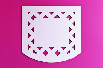 white mexican perforated paper on pink background