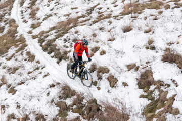 Cyclist in Red Riding Mountain Bike on the Snowy Trail. Extreme Winter Sport and Enduro Biking Concept.