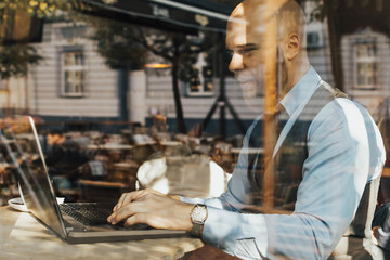 Young businessman in the cafe with reflection in the window