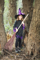 little witch outdoors in halloween with broom