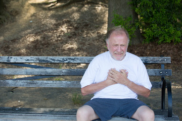 Closeup portrait, old man clutching chest, having heart pain, sitting on bench, isolated outdoors, green trees background. Myocardial infarction, aortic aneurysm rupture