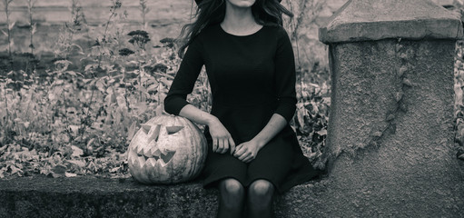 Happy creepy unrecognizible gothic young woman in witch halloween costume with halloween pumpkin