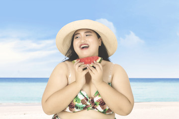 Fat woman eats watermelon on beach