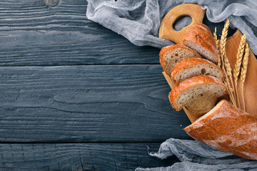 Assortment of bread and baking. On a wooden background. Top view. Free space for your text.