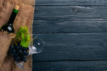 A bottle of wine and grapes. On a wooden background. Top view. Free space for your text.