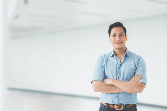 Confident Asian man smiling with arm crossed in modern office building