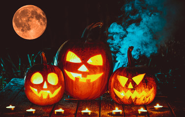 Halloween pumpkins on a wooden table in an eerie forest at night against of the bloody moon