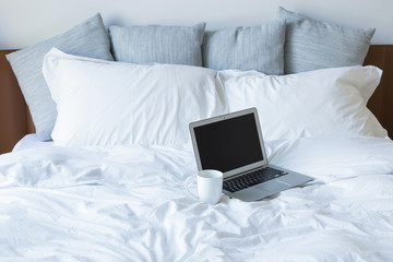 Laptop pc and cup of coffee on the bed