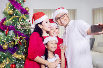 Cheerful family taking selfie on Christmas day