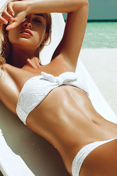 fashion photo of beautiful tanned woman with blond hair in elegant white bikini relaxing on white chair.