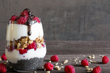 raspberry yogurt parfait in a glass with chocolate, granola and chia seeds for healthy breakfast