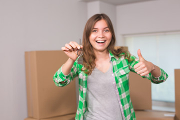 Happy apartment owner or renter showing keys and making thumbs up gesture
