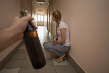 Woman victim of domestic violence and abuse. Woman scared of a man holding a bottle