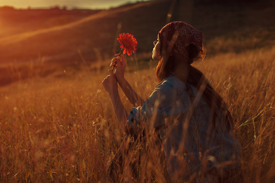 Young woman hold flower and enjoy the sunset in nature