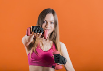 Beautiful dark hair girl, wearing a pink top, is training her arm biceps with dumbbells in the orange background, isolated, slow motion