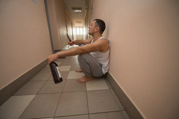 drunk aggressive man sitting on the floor and holding a knife and a bottle of alcohol in his hands