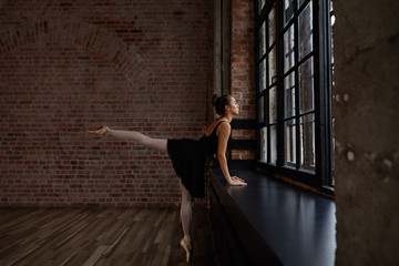People, ballet dance, art and theatre. Candid shot of beautiful graceful young European female ballet dancer wearing black tutu skirt, white stockings and pointe shoes practicing in spacious studio