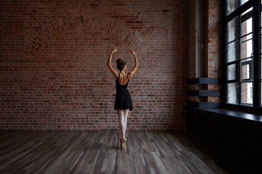 People, art, theatre, choreoography and dance concept. Back view of slender beautiful young ballerina in black dress standing en pointes in the middle of ballet studio, practicing center work