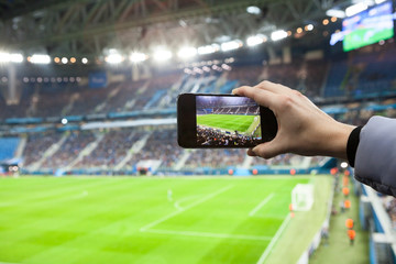 Fan hand with smartphone photographing footbal game