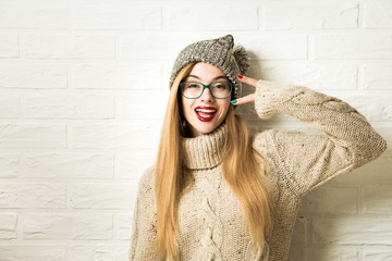 Trendy Hipster Girl in Knitted Sweater and Beanie Hat Going Crazy at White Brick Wall Background. Funny Female. Casual Fashion Outfit in Winter. Toned Photo with Copy Space.