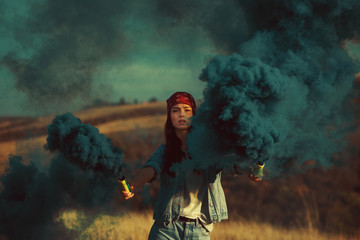 Young woman with smoke bombs in hands in a meadow