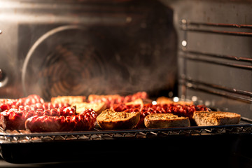 Delicious homemade sausage with bread rolls baked in the oven with a shallow depth of field.