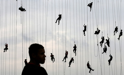 People climb after jumping off a bridge, which has a height of 30 meters, in Hortolandia