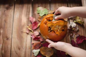 pumpkin in the hands, for the autumn holiday. on a wooden brown background with autumn leaves
