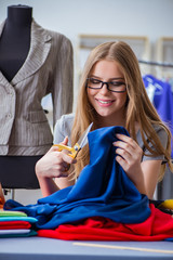 Young woman tailor working in workshop on new dress