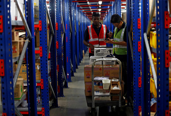 Employees work at RedMart's fulfillment centre in Singapore