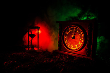Time concept. Silhouette of Hourglass clock and old vintage wood clock with arrow and smoke on dark background with hot yellow orange red blue cold back lighting, or symbols of time