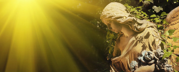 Majestic view of statue of golden angel illuminated by sunlight against a background of dark background. Dramatic unusual scene. Retro filter and vintage style.