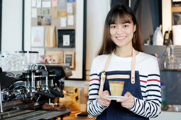 Young asian women Barista serving coffee cup with smiling face at cafe counter background, small business owner, food and drink industry concept