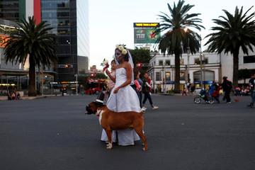 "A woman dressed up as ""Catrina"", a Mexican character also known as ""The Elegant Death"", stands with her dog during a Catrinas parade in Mexico City"