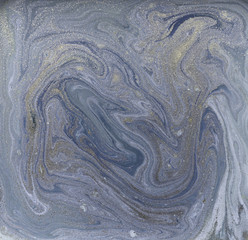 Liquid gold marbled pattern. Pale blue background.