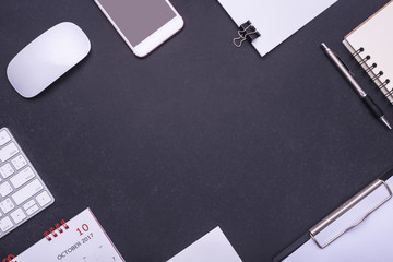 Office equipment, mouse, keyboard, smartphone, blank paper note, pen and calendar on black stone table. Middle free space for text or design
