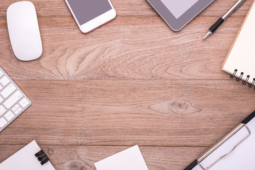Office equipment, mouse, keyboard, smartphone, tablet, paper note, pen and calendar on bright wooden desk. Middle free space for text or design