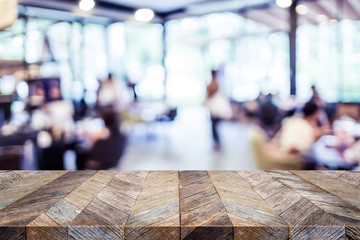 Empty rustic old wood table and blurred people dining at restaurant with bokeh light background. product display template.Business presentation.