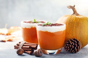 Pumpkin smoothie in glasses with cinnamon and acorns on wooden table