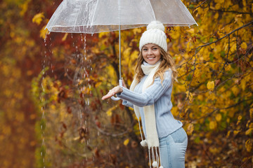 Very beautiful woman under the umbrella in autumn rainy day. Young pretty girl in the fall time. Cheerful girl outdoors