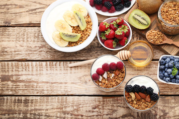 Tasty granola with berries in glasses and bowl on wooden table