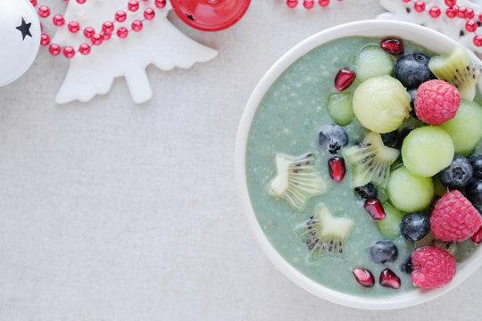 Blue spirulina smoothie bowl with melon, kiwi fruit, raspberries and blueberries, christmas festive fun food