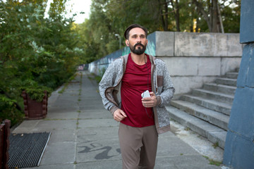 Healthy lifestyle, jogger in urban park. Mature male outdoors doing cardio workout.