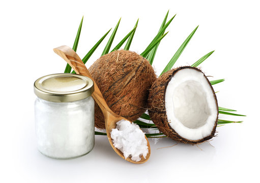 Coconut, glass jar and wooden spoon with coconut oil isolated on white background.