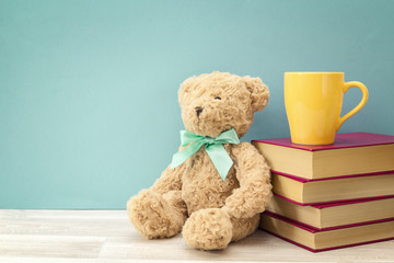 Plush bear with stack of book and yellow mug against blue background. Copy space for text.