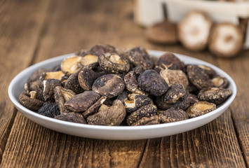 Portion of Shiitake mushrooms (dried) on wooden background, selective focus