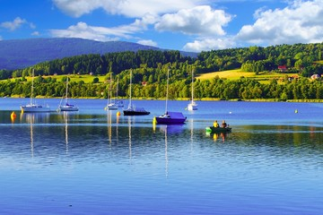 Boats illuminated by the sun in Lipno Lake with beautiful scenery in the background. Blizsi Lhota, Czech Republic.