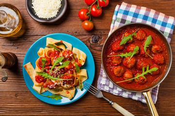 Italian pasta pappardelle with meatballs in tomato sauce.