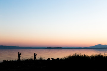Silhouettes of a couple on a lake shore taking photos of sunset with their cell phones
