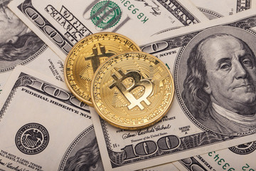 Two golden Bitcoins on US dollars